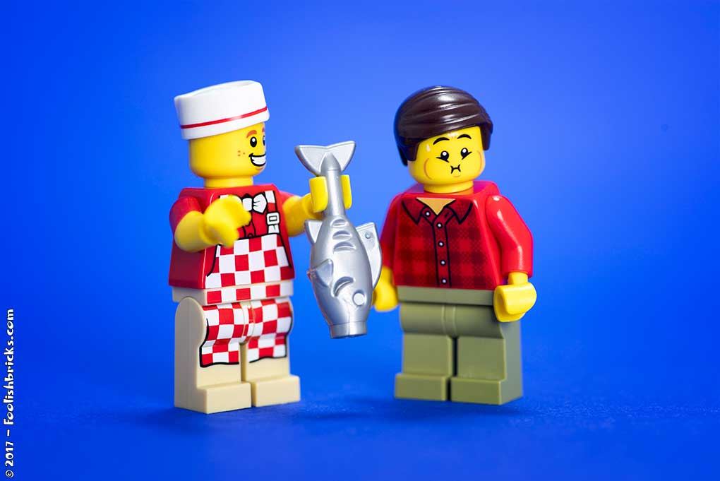 lego cook shows fish to nauseous disgusted man