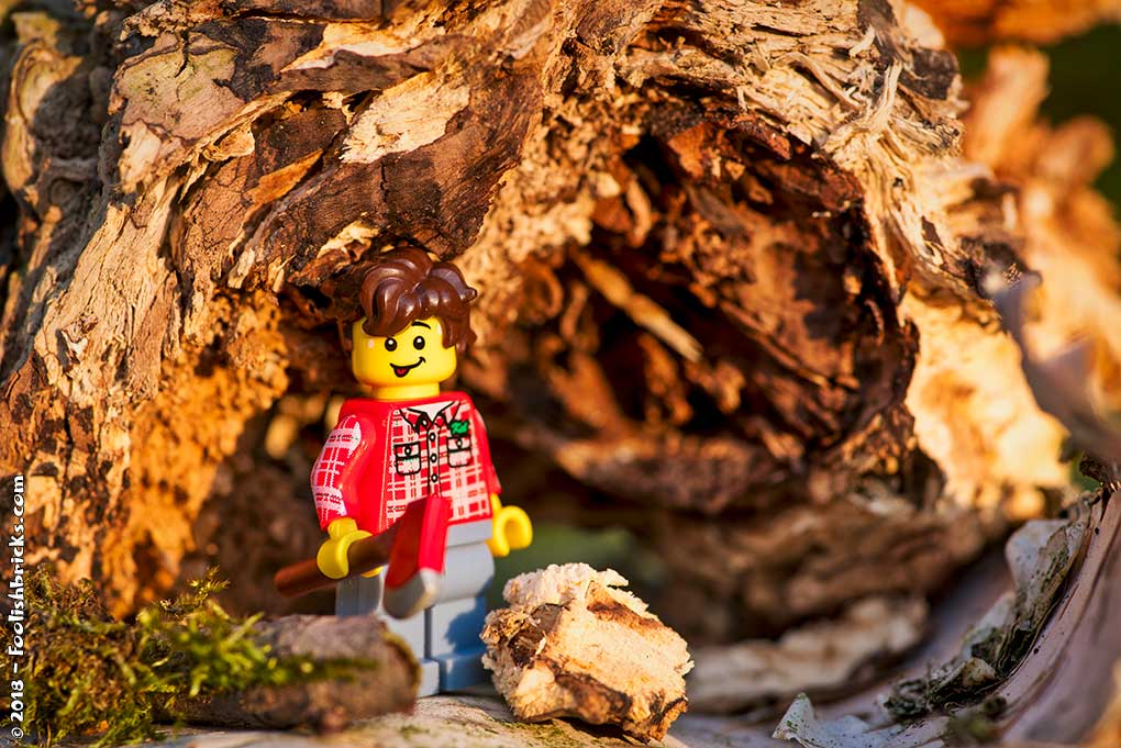 A lego person with an axe chopping wood