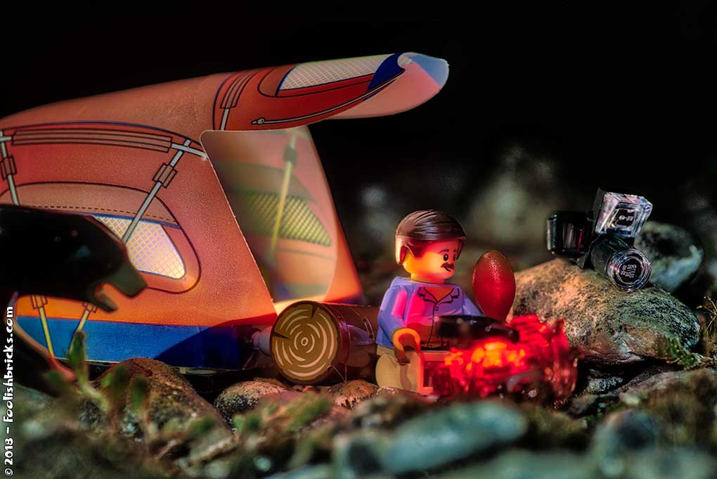 Lego man eating chicken in front of a tent at night, when suddenly a bear shows up.